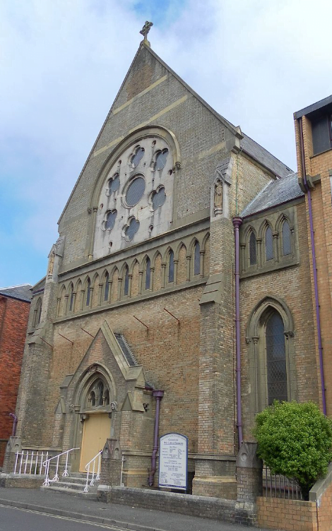 A tall gothic-style church, grey stone and slate roof