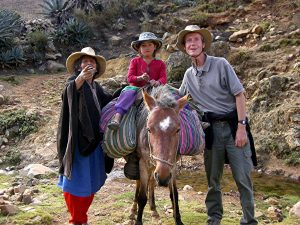 Fr Kevin standing next to to Peruvians (one child on a mule and one adult next to him)