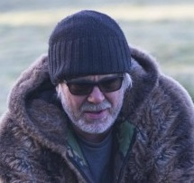 A man outside in a warm hat, coat and sunglasses.